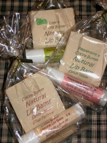 Three packages of all natural lip balm tubes are presented in compostable packaging from the Sandy Hook Soap Factory.  The label varieties read natural cocoa butter, lime and peppermint in these inexpensive truly natural beeswax lip balms free from petroleum wax, propylene glycol and chemical flavours and scents.