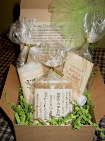 An open gift box is displayed with three all natural personal care items from the Sandy Hook Soap Factory hand made in Manitoba Canada from only wholesome ingredients.  The all natural soap, natural lip balm and bath salts are presented on a recycled shredded paper in an attractive green with a tulle ribbon.  The hand made artisan soap has obviously been made with care with no parabens, no propylene glycol, no SLS, no petroleum ingredients and no phthalates and would make a lovely inexpensive gift.