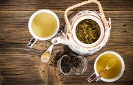 A relaxing display of Chinese tea.  Organic loose leaf green tea in a teapot with cups filled with freshly brewed tea and an open tea ball available at Organic Teas Canada.