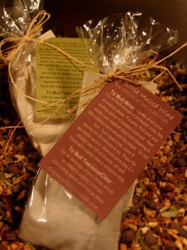 An organic gift presentation, single organic cotton bags containing fresh and fragrant organic mulling spices are presented in compostable cello bags with maroon and green wine mulling instructions attached with natural raffia. The bags are displayed on a bed of organic mulling spices which are non-GMO, non-suphited, non-irradiated and also contain no gluten.  Organic Teas Canada dot com photo.