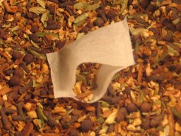 Beautifully coloured organic mulling spices are pictured with a partially full open tea bag in this photo from Organic Teas Canada dot com.  Single use tea bags full of quality, organic mulling spices for mulling tea, juice or cider in a convenient, easy and neat tea bag presentation.